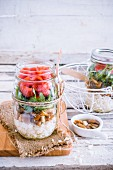 Rice salad with mushrooms, rocket and tomatoes in a glass jar