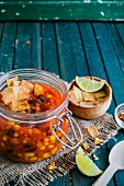 Vegan chilli in a glass jar with tortilla chips