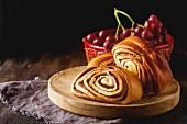 Französisches Brot auf Holztisch vor roten Trauben