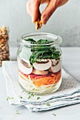 Raw salad in a jar, cabbage, carrots, radish, champignons and spinach, vegan