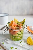 Lunch in a jar, green salad with avocado, cucumber, cress and letuce with smoked salmon and lemon.
