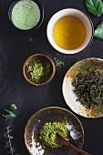 Stillleben mit Matcha Latte, grünem Tee, Matchapulver und Teeblättern