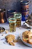 Two glasses of tea with turkish sweets on a marble background.
