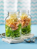 Lettuce with smoked salmon in glass jars