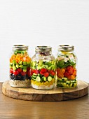 Various vegetable salads in a screw-top jars
