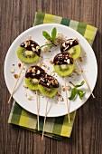 Schokoladen-Kiwi-Lollis mit gehackten Nüssen