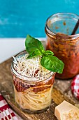 Spaghetti with roasted tomato sauce and parmesan in a glass jar