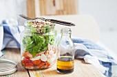 Gemischter Salat mit Datteltomaten, Minimozzarella, Stremellachs, Kopfsalat, gerösteten Haselnüssen mit Vinaigrette aus Balsamico und Haselnussöl im Glas