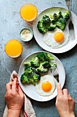 Steamed broccoli with parmesan cheese, fried eggs and a glass of orange juice for breakfast