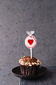 A cupcake with chocolate icing and oats with a heart-shaped lolly stuck in the top