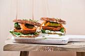Vegan burger with tofu patty, gherkins, lamb's lettuce, carrot and cress