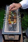 Chef grilling chicken on a Charcoal Konro Grill with Net