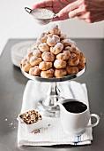Hands shaking powdered sugar onto tray of cream puffs