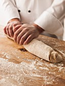 Hands of baker rolling dough