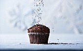 Brown sprinkles falling on chocolate cupcake
