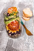 Quinoa salad in a glass jar with red cabbage, chickpeas, avocado, blood orange and cress