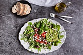 Quinoa salad with rocket, avocado, feta cubes, sugar snaps and tomatoes