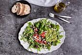 Quinoasalat mit Rucola, Avocado, Fetawürfeln, Zuckerschoten und Tomaten