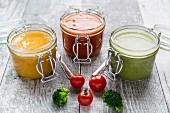 Various colourful soups in glass jars (broccoli soup, tomato soup, pumpkin soup)