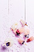 Ice lollies with berries, edible flowers and pomegranate seeds