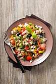 A salad with tuna, rice, tomatoes, beans, peppers and olives