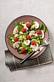 A mushroom salad with spinach, beans, peas and raspberries
