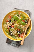 Pasta salad with cherry tomatoes, arugula, olives, ricotta and pine nuts