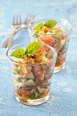 Tomato tartare with apple, pesto and basil in glasses