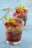Cherry desserts in glasses with almond crumbs and pistachios