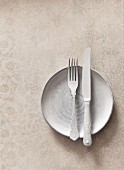 White cutlery on a white plate on a textured stone surface