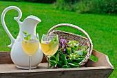 Apfelsaft mit Zitrone und frischen Kräutern in Gläsern und Krug auf Holztablett