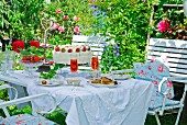 A romantic coffee table with a strawberry cake in a summer garden