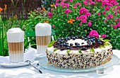 Blueberry and mascarpone pie with latte macchiatos on a table outdoors