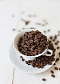 Coffee beans in a coffee cup and on a saucer