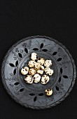 Quail eggs in a black metal bowl against a black background
