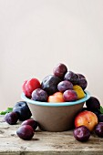 Plums in an earthenware bowl against a peach colour background