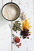 Raisins, golden raisins, pumpkin seeds, sunflower seeds and goji berries in small piles, and a bowl of oats