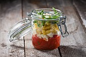 Fusilli with tomato sauce, mozzarella and rocket in a glass jar