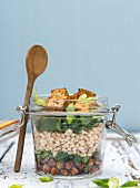 Vegan chickpea and barley salad with crispy tofu in a glass jar