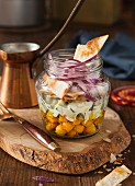 Curried chickpea packed lunch complete meal in a lunch jar on a wooden choppin board