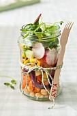 Vegetarischer Gemüsesalat im Glas mit daran gebundener Holzgabel