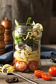 Italian style pasta salad in a lunch jar being eaten with tagliatelle wrapped around a folk in a rustic setting