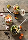 Three different lunch jar ideas with different fillings on a grey wooden table