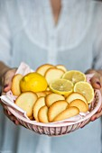 A woman holding a plastic bowl of lemon biscuits