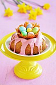 A gugelhupf with a pink sugar glaze and a caramel nest with colourful sugar eggs on a stand, with daffodils in the background