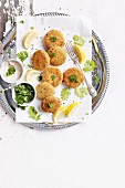 Fish Burgers with Lemon Wedges and Parsley on a white table