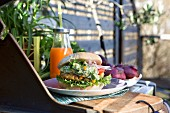 A chicken burger with a panko crust, avocado cream and salad on a table outdoors