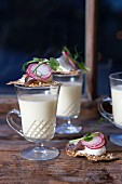 Cauliflower cream soup in glasses with crackers topped with herring cream cheese and radishes