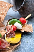 Tomato, mozzarella, ham and basil skewers with crispbread