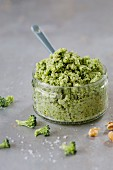 Broccoli and walnut pesto in a glass ramekin with a ceramic spoon